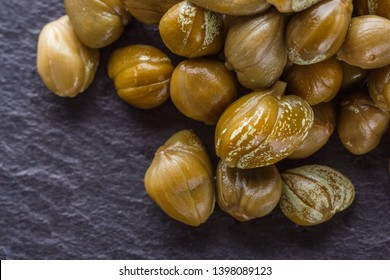 pickled capers on a dark stone background