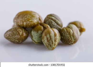 Pickled capers on a white acrylic background
