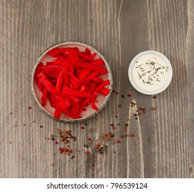 Pickled carrots in cranberry juice on wooden background