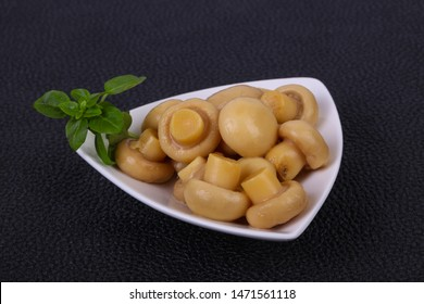 Pickled champignon heap in the bowl served basil leaves