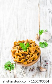 Pickled chanterelle mushrooms on wooden bowl on rustic background. Selctive focus, space for text.