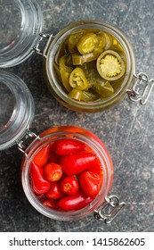 Pickled chili peppers and jalapeno peppers in jar.