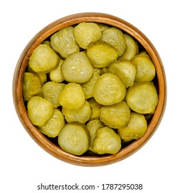 Pickled cucumber discs, also known as pickle or gherkin, in wooden bowl. Small pickled cucumbers with bumpy skin, sliced. Baby pickles. Close-up from above, over white, isolated macro food photo.