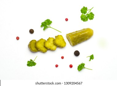 pickled cucumber sliced next to parsley leaves and peppers on white background