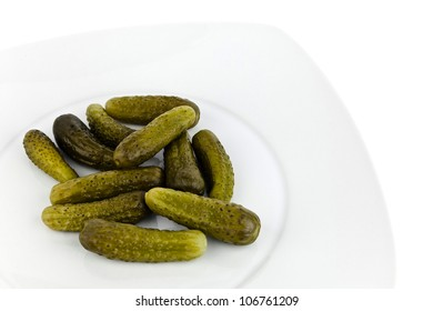 Pickled cucumbers in dish on white background.