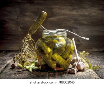 Pickled cucumbers with herbs and spices. On a wooden background.
