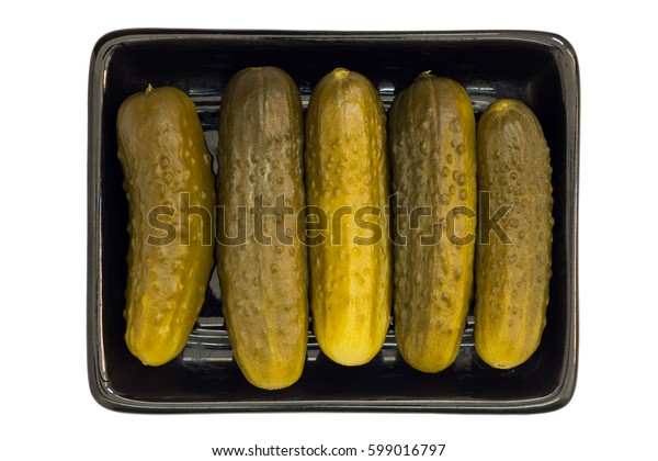 Pickled cucumbers on  black dish.