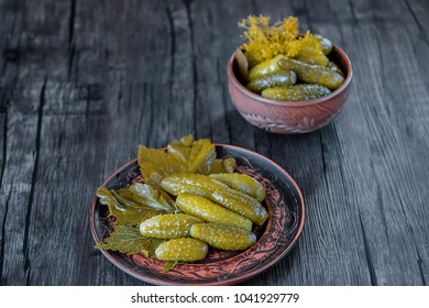 Pickled cucumbers on brown plate. Soft focus.