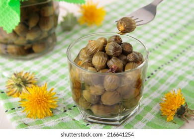 Pickled flower buds of dandelions in a glass and jar