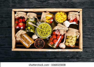 Pickled foods in cans. Stocks of food. Top view. On a wooden background. Copy space.