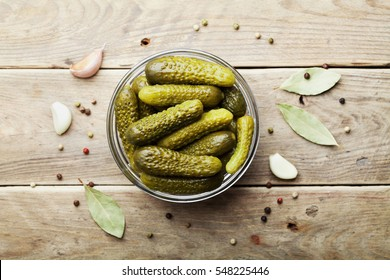 Pickled gherkins or cucumbers in bowl on wooden rustic table from above.