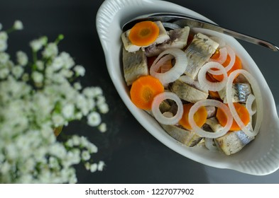 Pickled herring with onions and carrots - traditional Lithuanian Christmas Eve dish, in the ceramic bowl