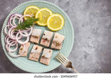 Pickled herring with red onion and lemon slices.