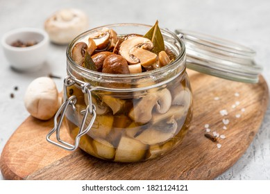 Pickled mushrooms in a glass jar close-up. Marinated mushrooms with pepper and bay leaf. Food preserving for autumn or winter time