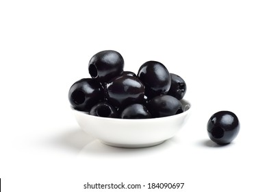 Pickled pitted black olives in a bowl isolated on a white background