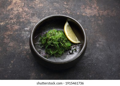 A pickled seagrass, seaweed Japanese salad with sesame, decorated with a lemon wedge. A goma wakame, top view, on a black stony background. A traditional oriental cuisine, sushi restaurant menu.