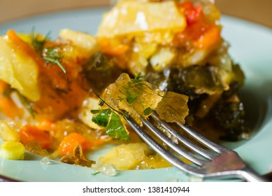 Pickled vegetable in aspic on green plate with fork, closeup.