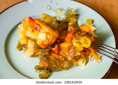 Pickled vegetable (carrot,onion,pepper) in aspic on plate with fork, closeup.