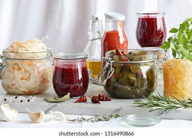 Pickled vegetables, berry marmalade, tomato sauce displayed on marble cutting board. Preseved vegetables and berries food concept. Vintage style