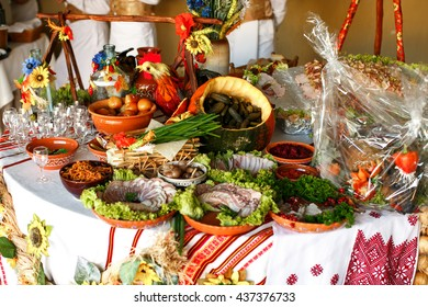 Pickled vegetables and cut meat lie on the table decorated in ethnic style