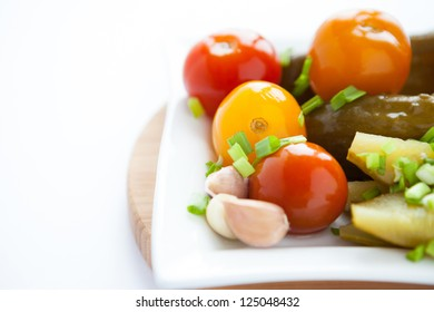 pickled vegetables on a white square plate, closeup