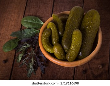 Pickles in a clay bowl on a dark rustic background with lettuce leaves