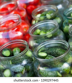 Pickling (canning) tomatoes and cucumbers. Glass jars with vegetables.