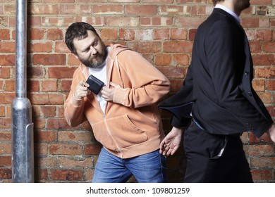 Pickpocket stealing a mans wallet from his back pocket walking down a street