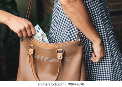 Pickpocket thief is stealing money from woman leather handbag