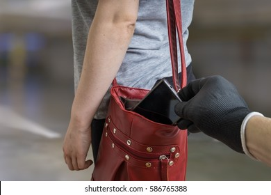 Pickpocket thief is stealing phone from woman from her handbag.
