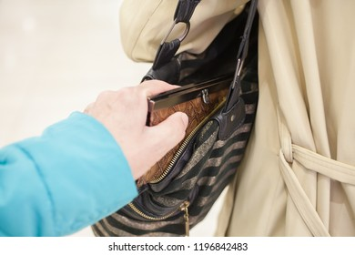 Pickpocket thief is stealing purse from handbag. selective focus