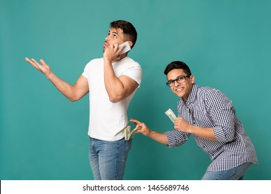Pickpocketing Concept. Thief Fishing Out Money From Man's Back Pocket While He's Talking On Phone. Turquoise Background.