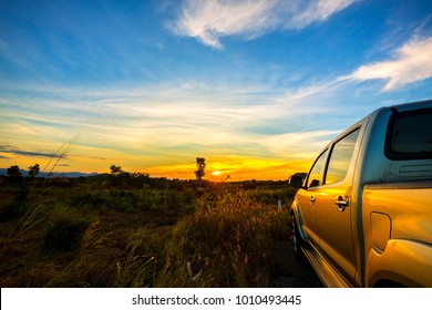 The pickup car parked in the meadow field with light of the sunset. The concept of driving along the countryside in the nature of travelers.