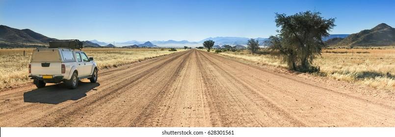 Pickup truck driving on long straight desert road towards mountains.