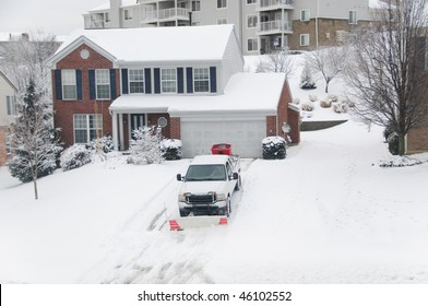 A pickup truck equipped with a plow and a salt thrower is removing snow from a sloped driveway in winter.