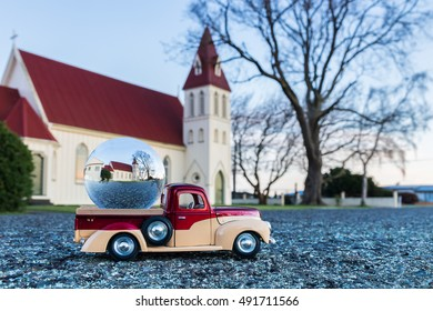 Pickup truck with a glass ball on it, with a church in side the ball.