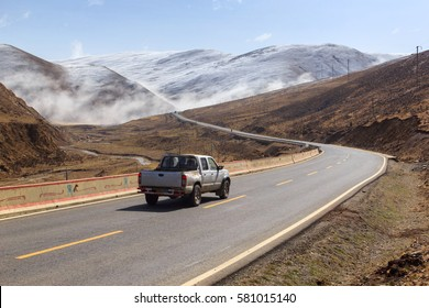 Pickup truck on the road, Beautiful winter road in Tibet under snow mountain Sichuan, China