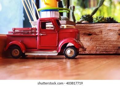 It is Pickup truck toy on wooden board.