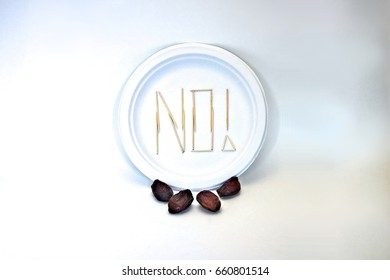"Picky Eater - Dates. Ingredients in focus sit against blurred plate of toothpicks spelling ""NO!"". Dietary restriction/picky eater visualization of focal ingredient rejected."