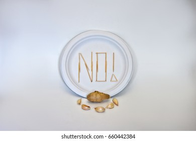 "Picky Eater - Garlic and Ginger. Concept of a picky eater/dietary restriction represented by toothpicks spelling out ""NO"" on a plate in rejection to the ingredients displayed in front."