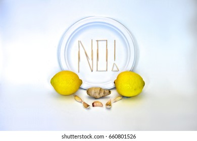 "Picky Eater -Lemon, Garlic, Ginger. Ingredients in focus sit against blurred plate of toothpicks spelling ""NO!"". Dietary restriction/picky eater visualization of focal ingredient rejected."
