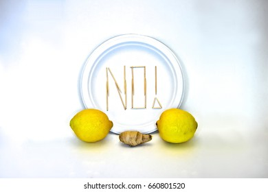"Picky Eater -Lemon, Ginger. Ingredients in focus sit against blurred plate of toothpicks spelling ""NO!"". Dietary restriction/picky eater visualization of focal ingredient rejected."