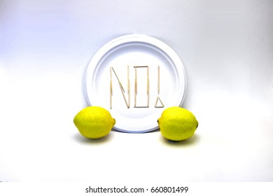 "Picky Eater -Lemon. Ingredients in focus sit against blurred plate of toothpicks spelling ""NO!"". Dietary restriction/picky eater visualization of focal ingredient rejected."