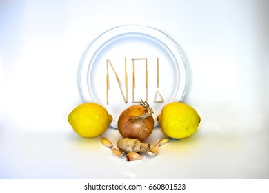 "Picky Eater -Lemon, Onion, Garlic, Ginger. Ingredients in focus sit against blurred plate of toothpicks spelling ""NO!"". Dietary restriction/picky eater visualization of focal ingredient rejected."