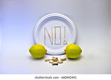 "Picky Eater - Lemons and Garlic. Concept of a picky eater/dietary restriction represented by toothpicks spelling out ""NO"" on a plate in rejection to the ingredients displayed in front."