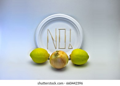 "Picky Eater - Lemons, Onion. Concept of a picky eater/dietary restriction represented by toothpicks spelling out ""NO"" on a plate in rejection to the ingredients displayed in front."