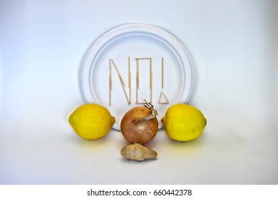 "Picky Eater -Lemons, Onion, Ginger. Concept of a picky eater/dietary restriction represented by toothpicks spelling out ""NO"" on a plate in rejection to the ingredients displayed in front."