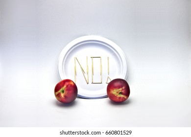 "Picky Eater -Nectarine Peaches. The ingredient in focus sits against a blurred plate of toothpicks spelling ""NO!"". Dietary restriction/picky eater visualization of focal ingredient rejected."