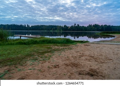 picnic area by the lake with wooden plank boardwalk in sunset with calm water