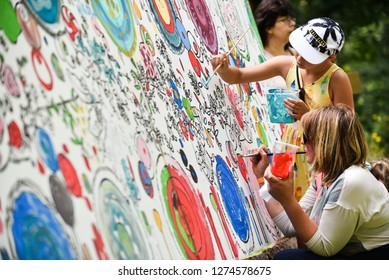 Picnic with arts elements. Little child painting color wall with brush. Rezekne - Latvia, July, 2018.